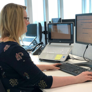 Female at desk on computer with laptop screen next to her
