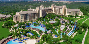 Overhead view of hotel complex with buildings, trees and swimming pools